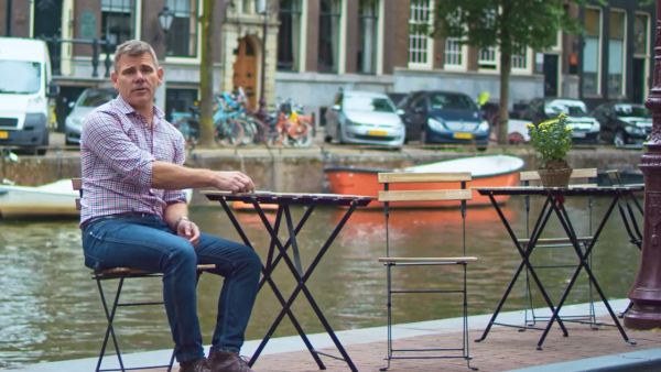 Man sitting at table beside canal in Amsterdam