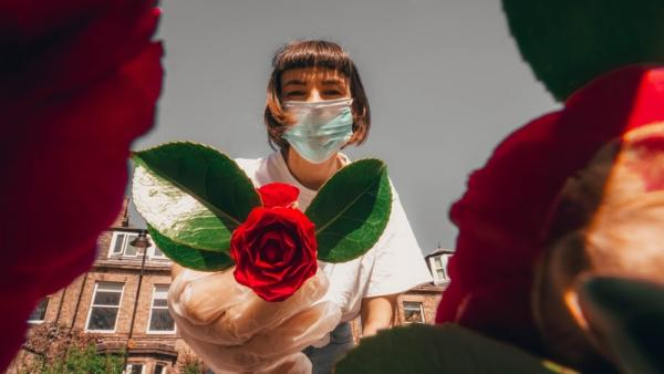 young woman in mask holding out red rose