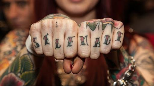 """SELF MADE"" tattoo across a woman's knuckles"